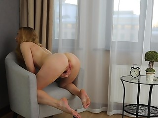 Unique blonde plays with her pussy on a chair